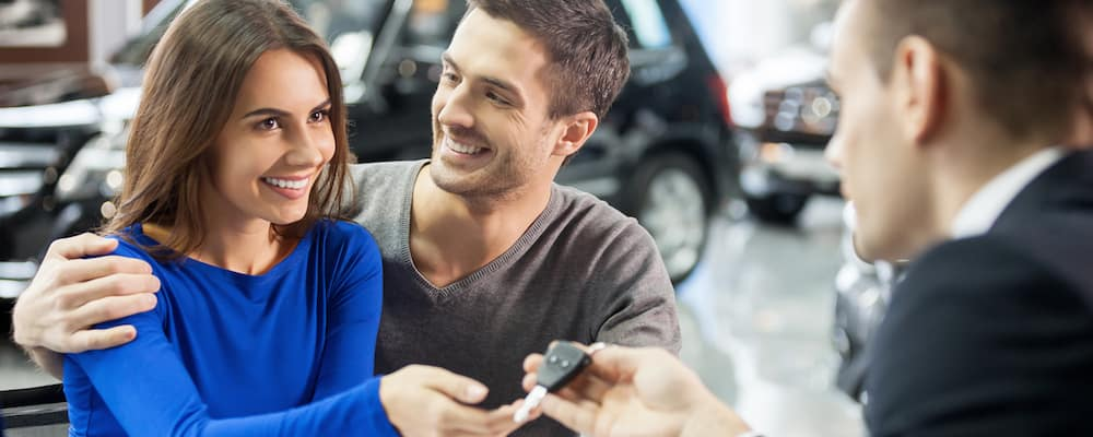 couple in dealership getting keys