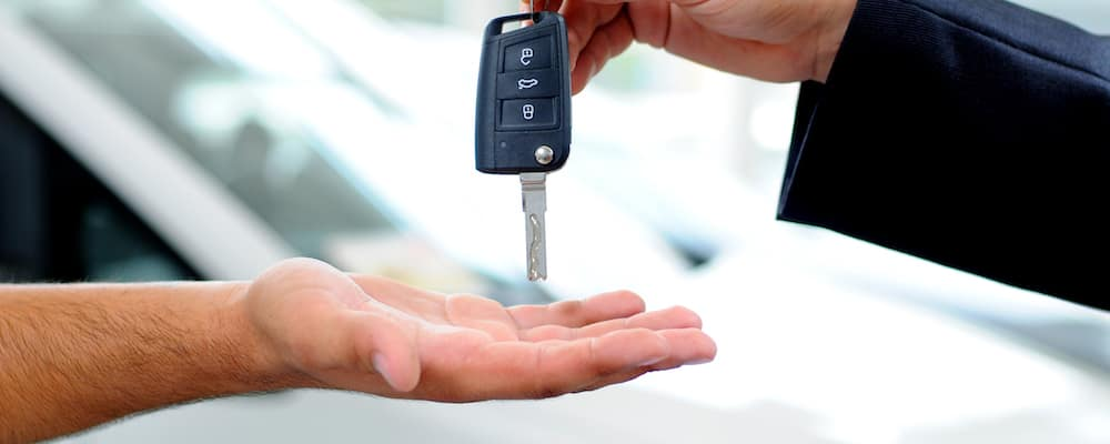A sales representative hands over the keys to a used Ford model.
