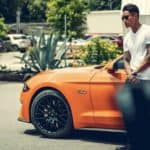 guy leans on ford mustang 5.0