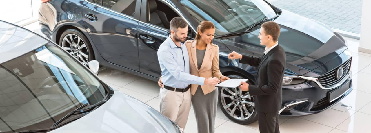 dealer hands couple car key in showroom