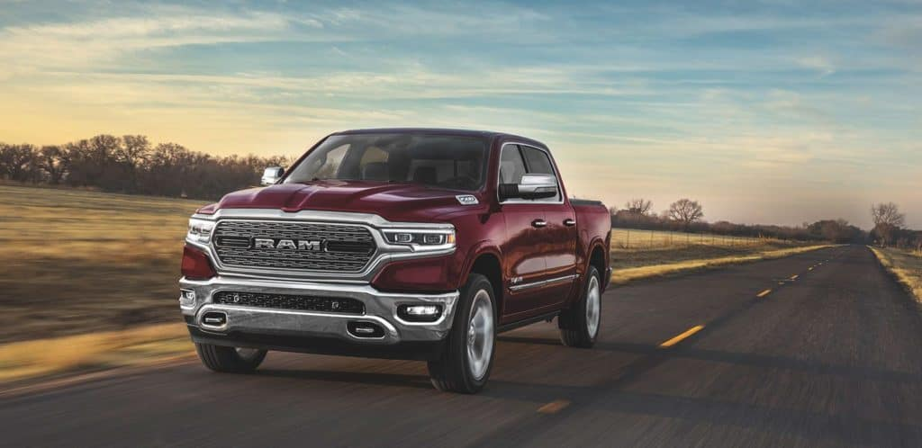 Maroon 2020 RAM 1500 driving down a highway through a field. Available now at Shaver CDJR of Thousand Oaks