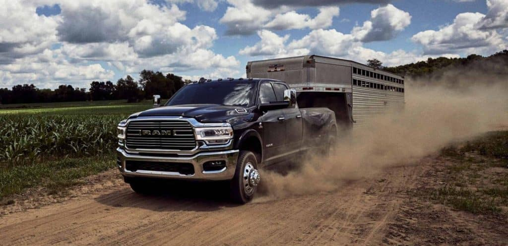 A blue RAM 3500 towing a horse trailer down a dirt road. Available now at Shaver CDJR of Thousand Oaks.