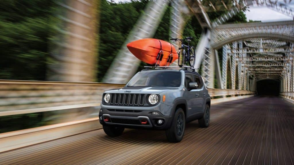2020 Jeep Renegade driving over a bridge with a kayak on its roof. Available now at Shaver CDJR.