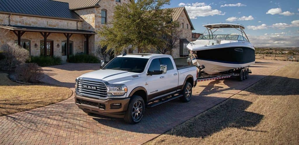 RAM 2500 towing a large boat near Shaver CDJR