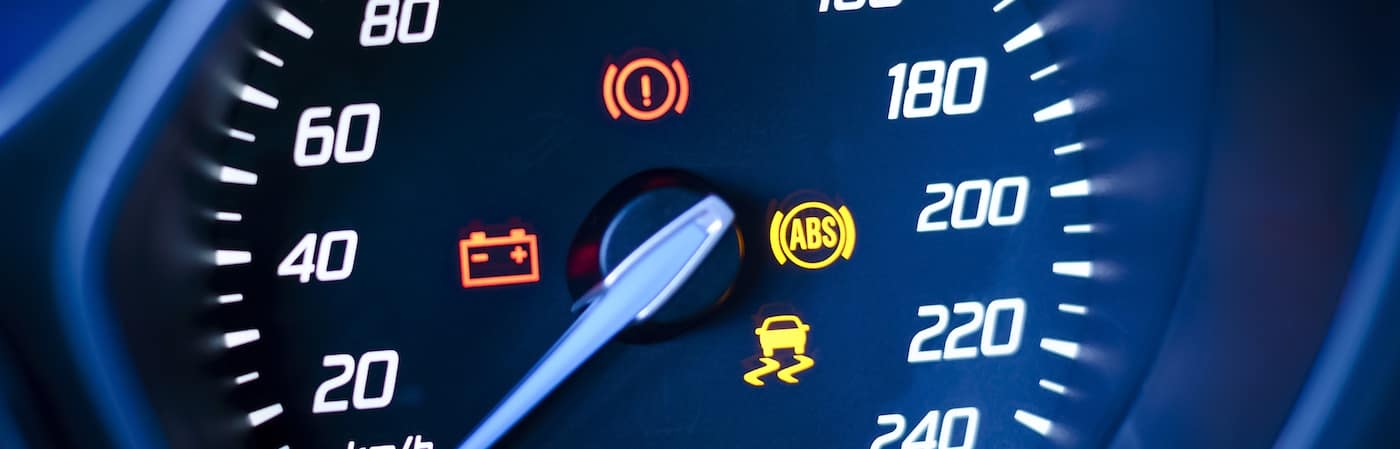 Photo presents car's speedometer or tachometer with visible information display - ignition warning lamp and brake system warning lamp, visible symbols of instrument cluster with warning lamps illuminated.