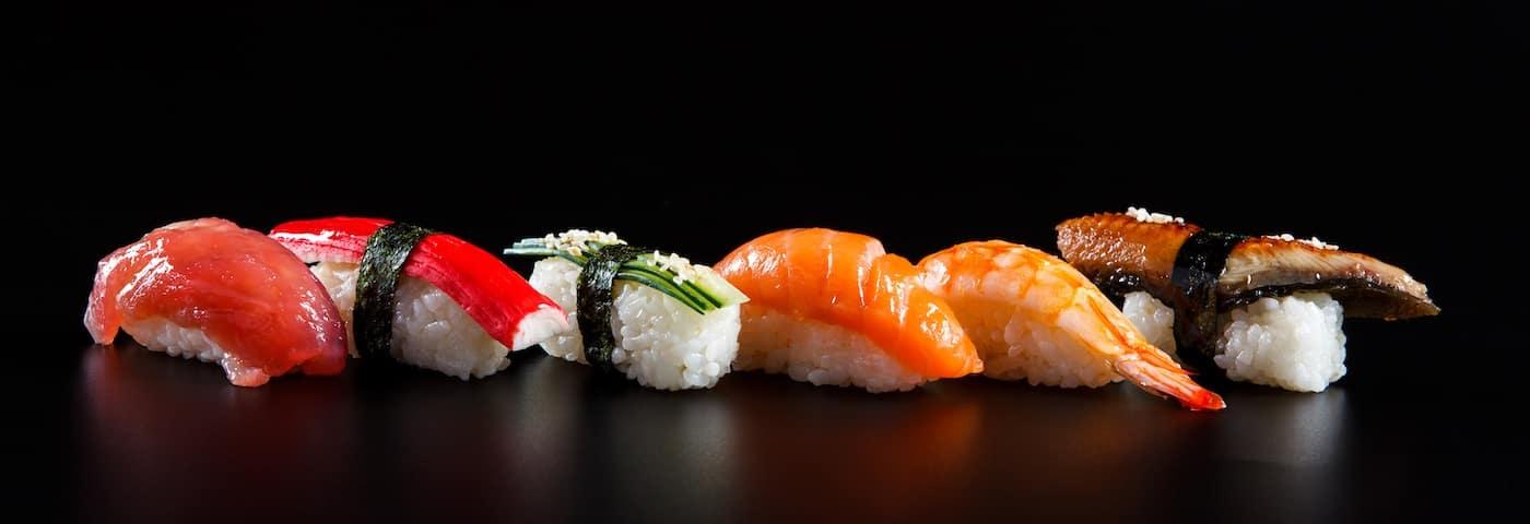 Line of sushi sashimi with salmon, eel, and more