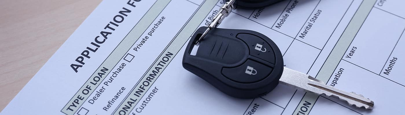 Application form for car loan and key on wooden table, close up view