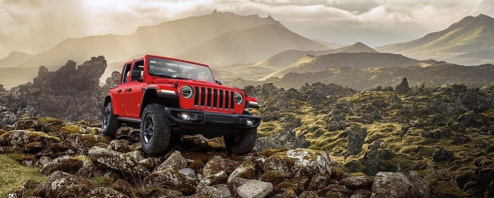 A 2020 Jeep Wrangler driving over large rocks near a mountain