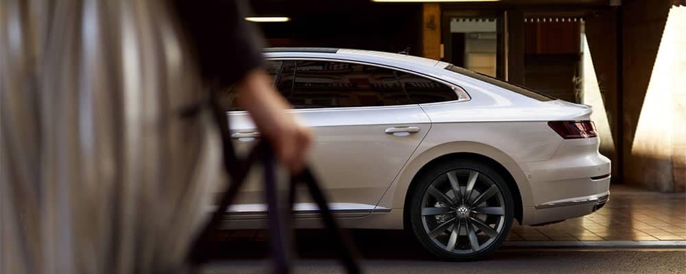 Woman walking to a Volkswagen Arteon