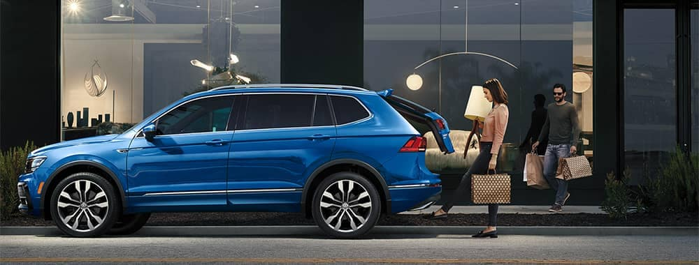 Couple loading things into cargo of Volkswagen Tiguan