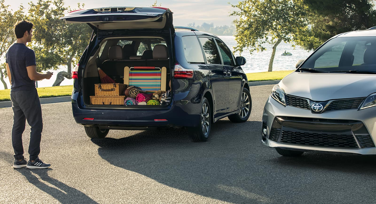 2 Toyota Sienna Minivans with trunk open storing items